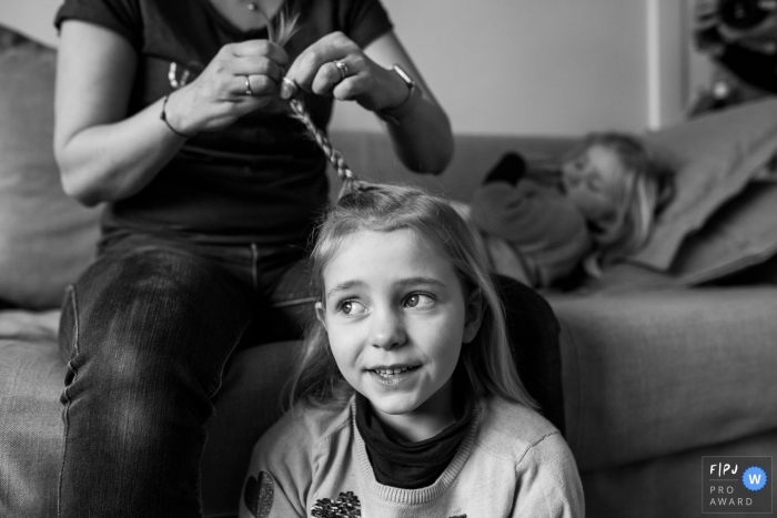 A mother braids her daughter's hair in this black and white reportage photograph by a Surrey, England family photojournalist.