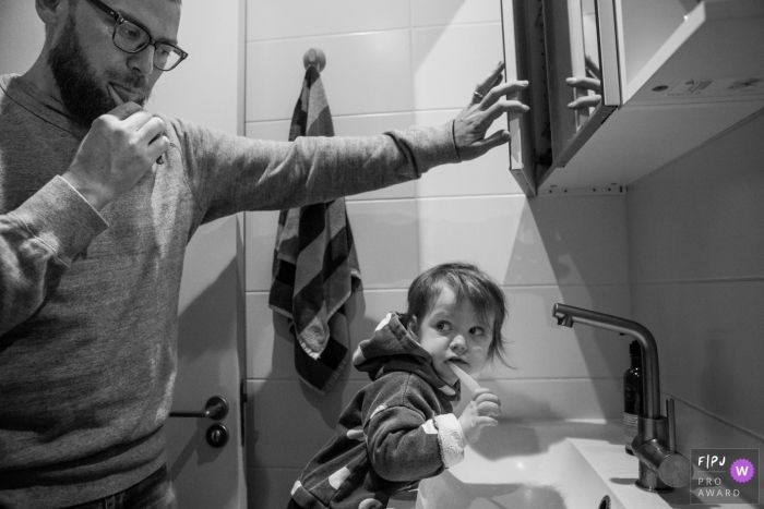A father and son brush their teeth together in this black and white photo by a Surrey, England family reportage photographer.