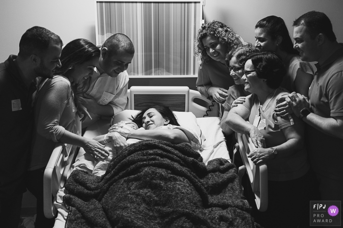 A family surrounds a woman in the hospital as she holds her newborn infant in this black and white birth picture by a Rio de Janeiro, Brazil photographer.