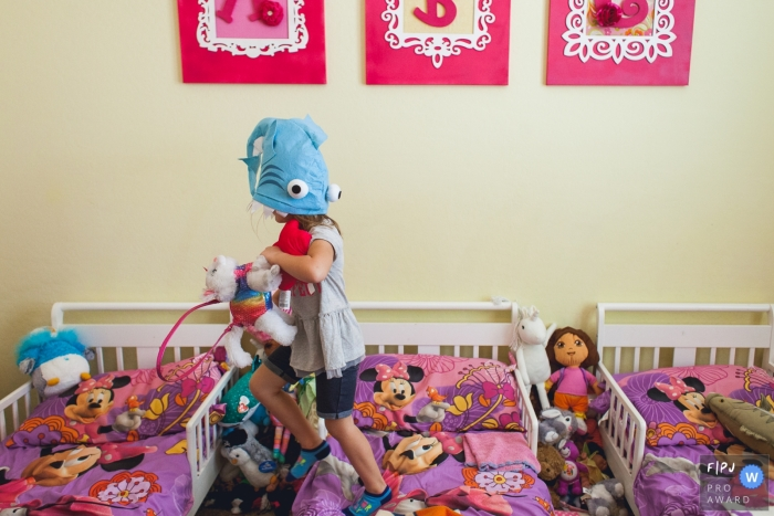 A little girl jumps on her bed with a toy fish on her head in this FPJA award-winning image captured by a Phoenix, AZ family photographer.