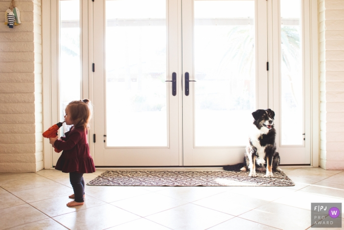 A little girl plays with a drill as a dog sits behind her in this award-winning photo by a Phoenix, AZ family photographer.