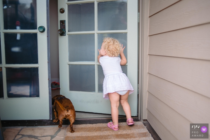 A little girl opens a door and lets the dog into the house in this Family Photojournalist Association awarded photo by a Omaha, NE documentary family photographer.