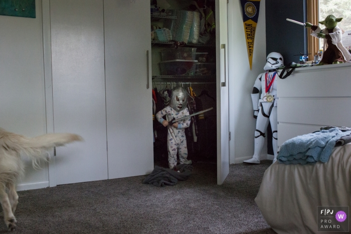 A little boy stands in his closet dressed as a knight in this FPJA award-winning image captured by a Boulder family photographer.