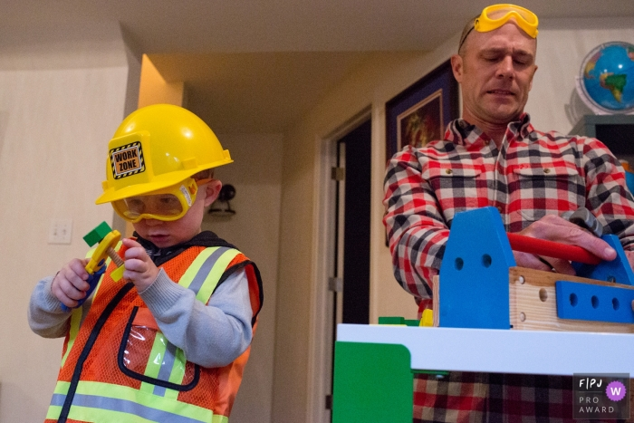 A father and son play with a building set in this award-winning photo by a Boulder, CO family photojournalist.
