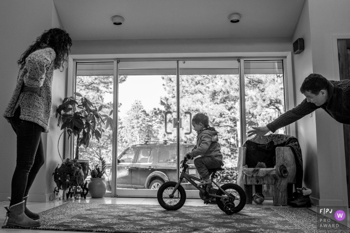 A father and mother teach their son how to ride a bike in this photo recorded by a Boulder, CO award-winning, documentary-style family photographer.
