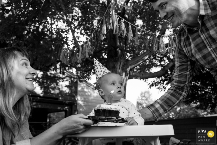 Boulder family photojournalist captured this picture of mom and dad excited to present their child with a smash cake for her first birthday