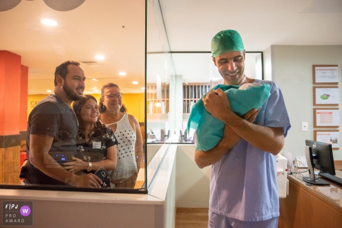A nurse holds a newborn up to the hospital window for the family to see in this photo by a Rio de Janeiro, Brazil reportage-style birth photographer.