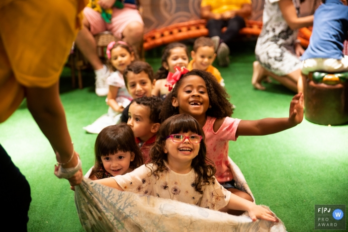 Children sit on a sheet and are pulled across the floor in this picture captured by a Rio de Janeiro, Brazil family photojournalist.