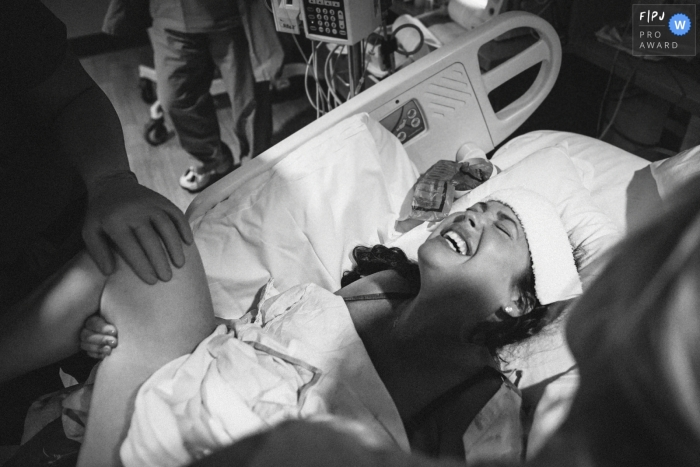 A mother gives birth in a hospital in this black and white awarded image by a Seattle, WA birth photographer.