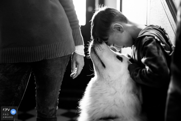 A little boy touches his forehead to his dog's nose in this photograph created by a Brussels family photojournalist.