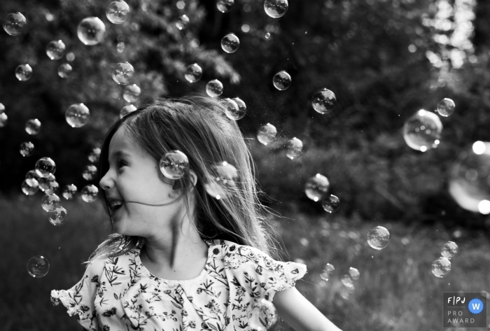 A little girl is surrounded by bubbles in this documentary-style family image recorded by a Brussels, Belgium photographer.