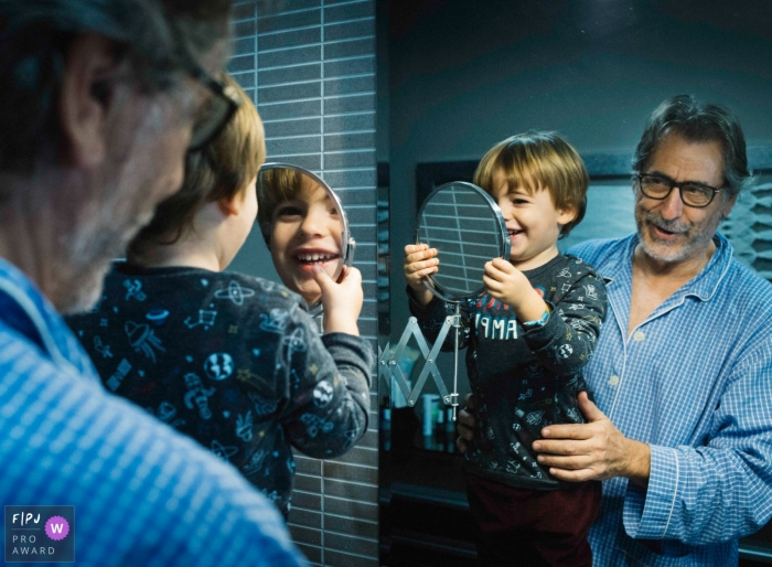 A little boy is held in front of a mirror as he holds a smaller one up to his face in this Family Photojournalist Association contest awarded photo created by a Valencia, Spain family photographer.