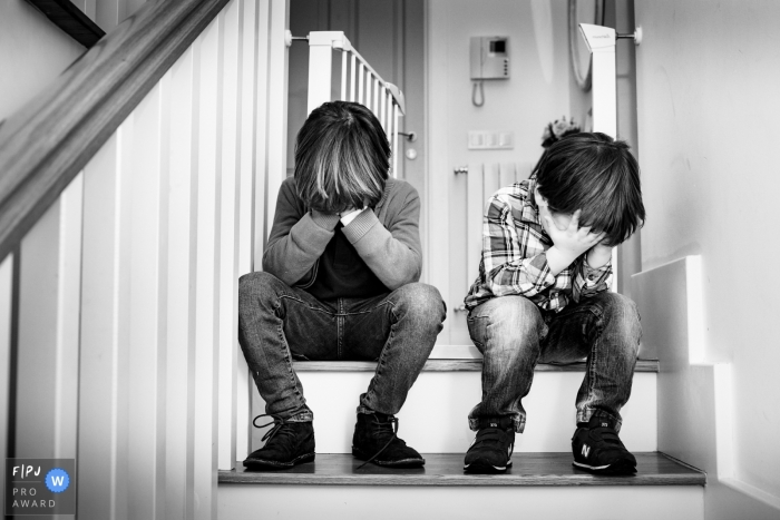 Two boys sit on the stairs covering their faces in this photo by a Valencia, Spain award-winning family photographer.
