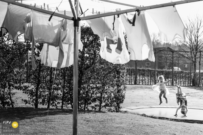 Eindhoven family photojournalist created this black and white image of young children playing on a trampoline while laundry hangs to dry in the foreground