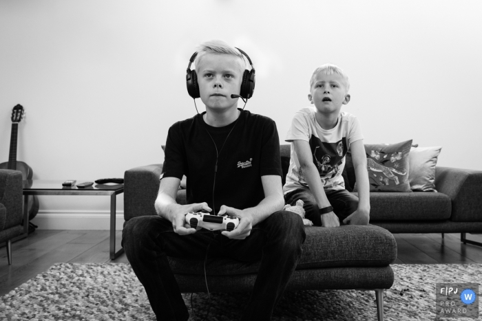 A boy plays video games while his brother watches in this black and white photo by a Cambridgeshire, England reportage-style family photographer.