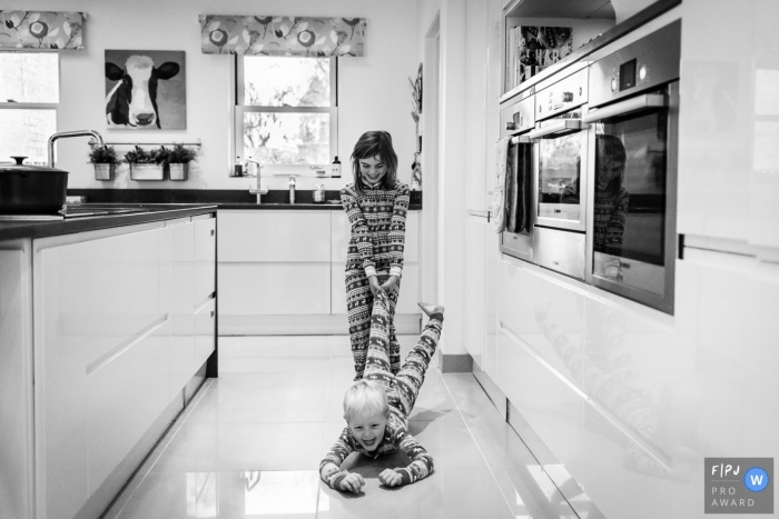 A girl pulls her brother along a tile floor in this black and white photo by a Cambridgeshire, English reportage family photographer.