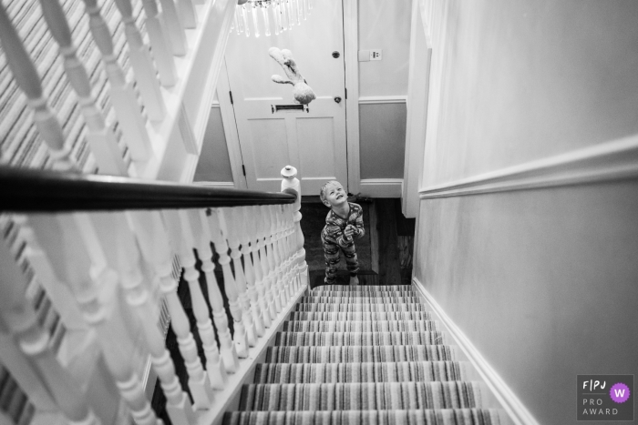 A little boy tosses his bear in the air at the bottom of the stairs in this black and white photo by a Cambridgeshire, English reportage-style family photographer.