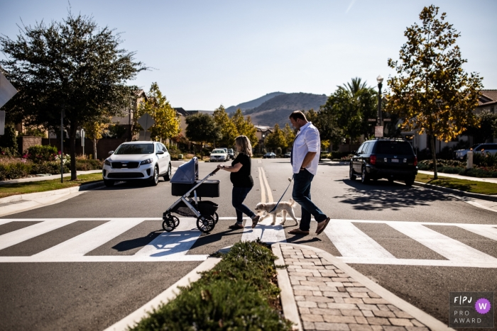 A mother and father cross the street with their dog and baby in this Family Photojournalist Association contest awarded photo created by an Orange County, CA family photographer.