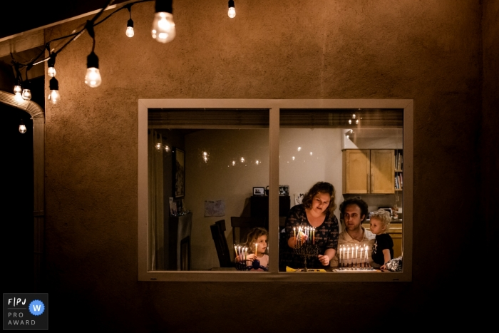 A family lights candles on a menorah inside their home in this FPJA award-winning picture by an Orange County, CA family photographer.