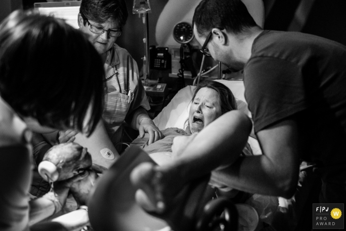 Noord Holland hospital photographer captured this emotional black and white photo of the mothers expression as she sees her baby for the first time just after birth