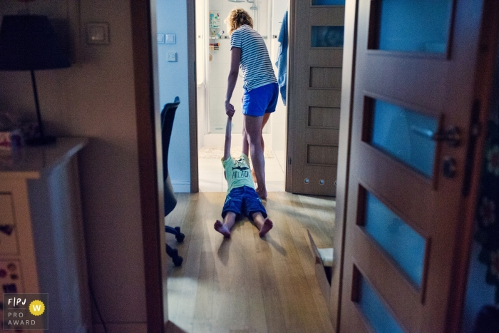 Warsaw family photojournalist created this image of a reluctant toddler being pulled to the bathroom for bathtime