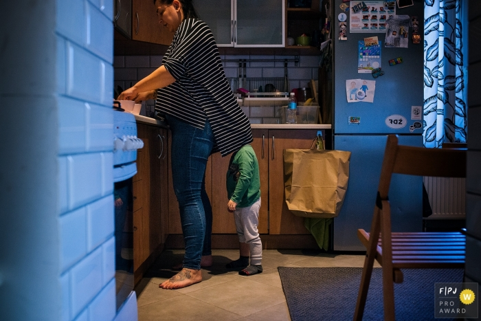Warsaw documentary family photographer captured this photo of a toddler using his mothers shirt as a shield as she cooks a meal in their kitchen