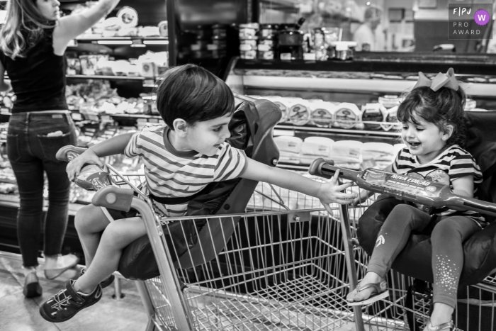 A little boy reaches back for his sister as they sit in grocery carts in this image created by a Minas Gerais family photographer.