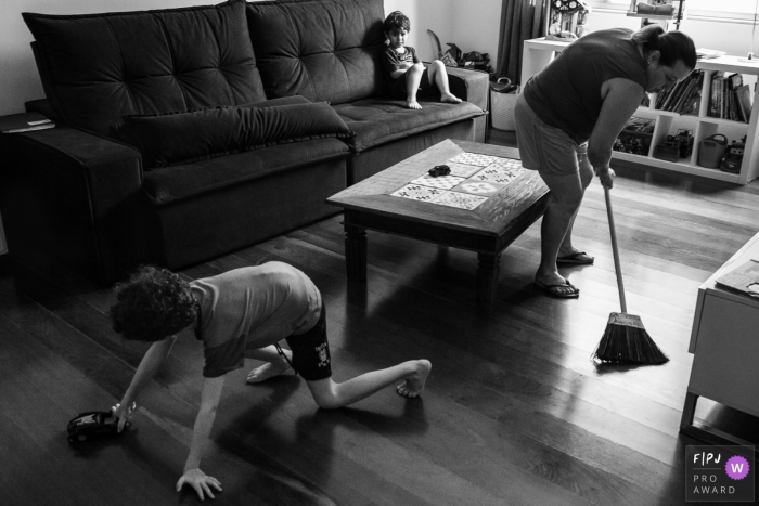 A mother sweeps the floor while one of her sons plays and the other sits on a couch in this image created by a Minas Gerais family photographer.