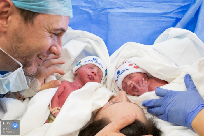 A father and mother hold their newborn twins in the hospital in this photograph captured by a Sao Paulo, Brazil birthing photographer.