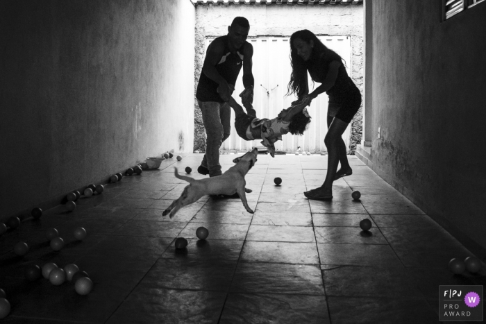 A mother and father swing their child between them as a dog runs over to them in this photo by a Minas Gerais award-winning family photographer.