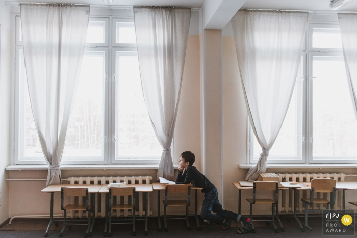 This photo of a young child staring out the window in a classroom was captured by a Saint-Petersburg family photojournalist