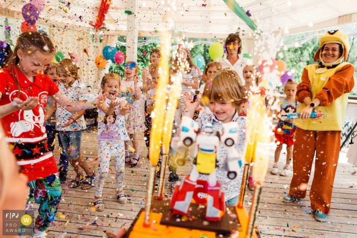 This portrait of a young boy in front of his robot birthday cake surrounded by family and friends throwing confetti was captured by a Saint-Petersburg family photojournalist