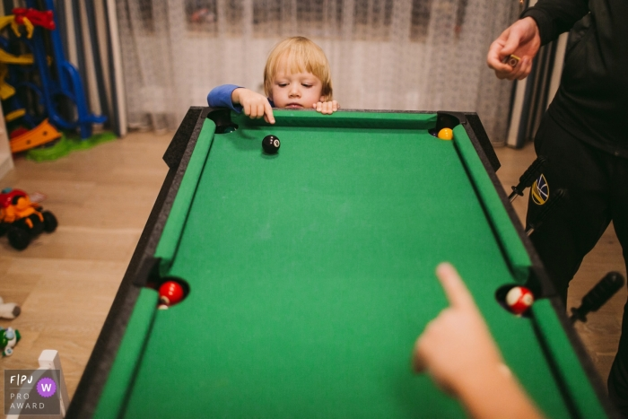 A little boy tries to touch a pool ball on a miniature pool table in this photograph created by a Saint Petersburg, Russia family photojournalist