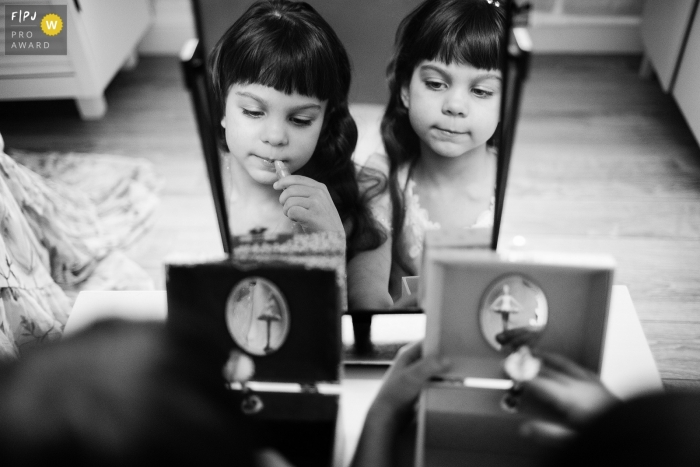 Saint-Petersburg family photojournalist captured this black and white picture of the reflection of twin girls playing with music boxes side by side