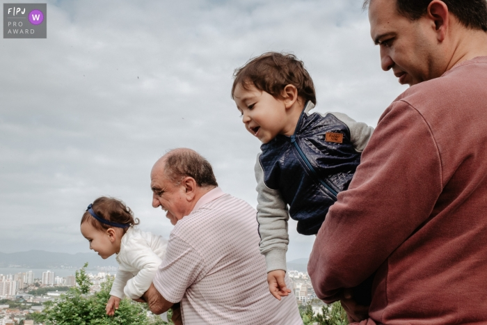A father and grandfather hold a little boy and his sister up so they can see the city in this photo by a Santa Catarina documentary-style family photographer.