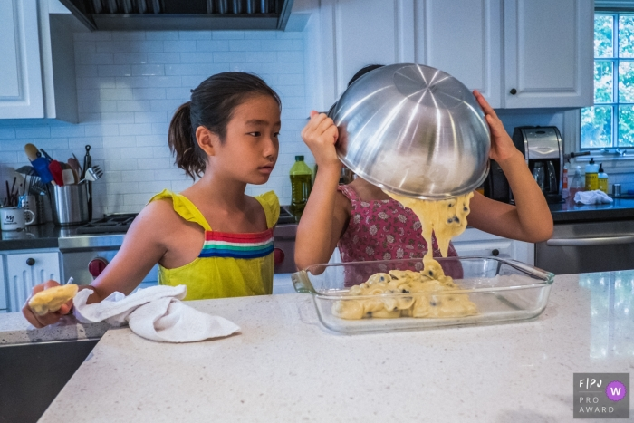 A girl pours batter into a baking pan as her sister watches in this Family Photojournalist Association awarded photo by a Los Angeles, CA documentary family photographer.