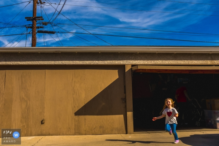 A little girl runs out of the garage in this award-winning photo by a Los Angeles, CA family photographer.
