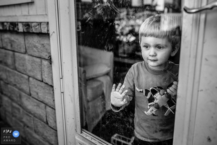 A young boy looks out the window as he holds a toy plane in this image created by a Los Angeles, CA family photographer.