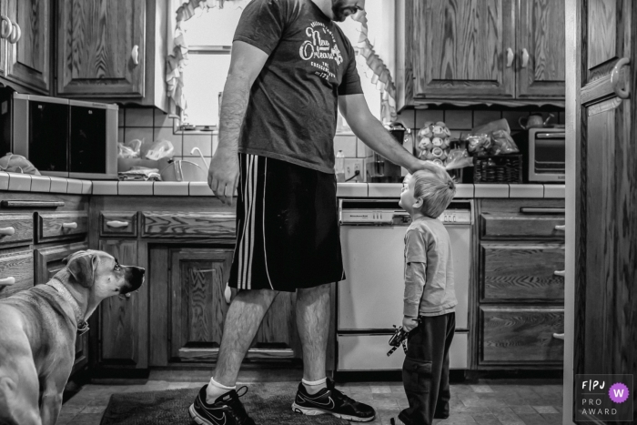 A father pats his son's head as the family dog watches in this photo recorded by a Los Angeles, CA award-winning, documentary-style family photographer.