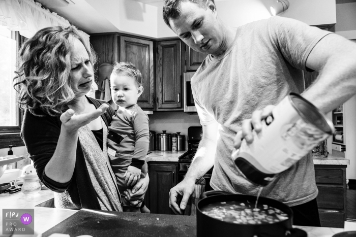 A mother and child look uncertain as a father pours canned soup into a pot on the stove in this FPJA award-winning picture by a Boulder, CO family photographer.