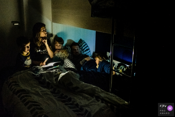 A mother uses her phone light to read a bedtime story to her sons while her husband sleeps in this FPJA award-winning image captured by a Rio Grande do Sul, Brazil family photographer.