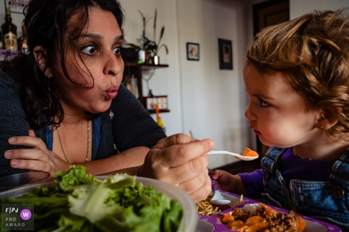 A mother makes faces as she tries to get her young daughter to eat in this photo recorded by a Rio Grande do Sul, Brazil award-winning, documentary-style family photographer.