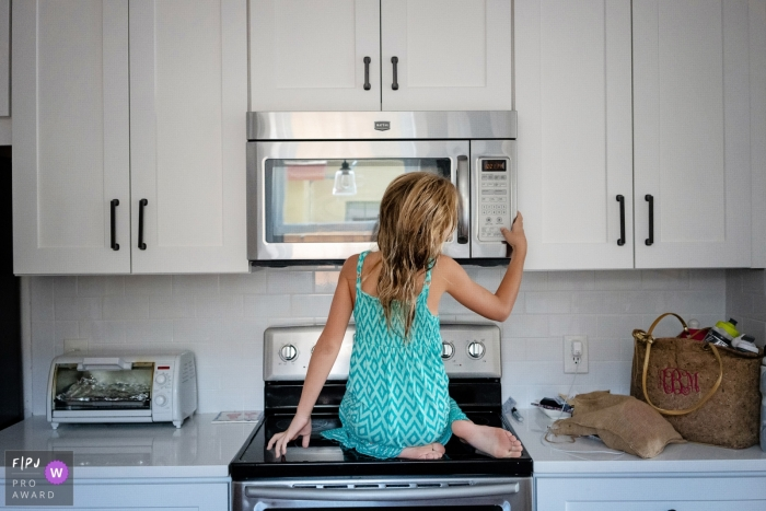 A young girl sits on the stove to reach the microwave in this Family Photojournalist Association contest awarded photo created by a Key West, FL family photographer.