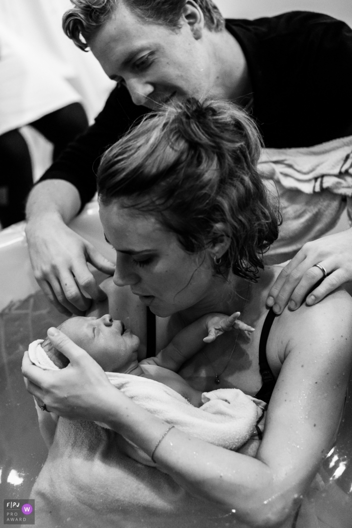 A father looks on as his wife holds their newborn infant in the birthing tub in this black and white image captured by an award-winning Copenhagen birth photographer.