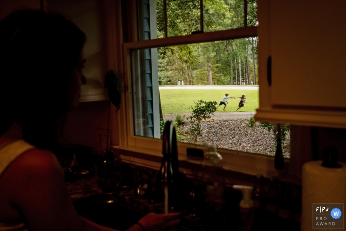 A mother watches her children play through the kitchen window in this documentary-style family photo captured by a Key West, FL photographer.