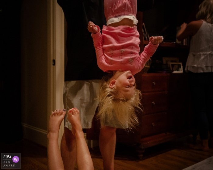 A father holds his daughter upside down as she laughs in this photograph by a Key West, FL documentary family photographer.