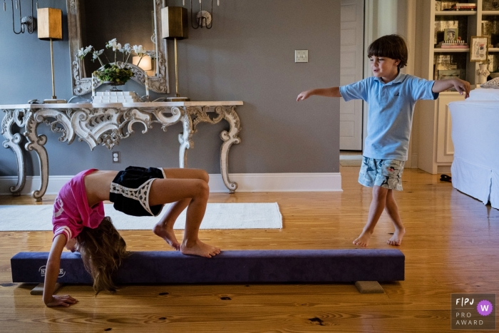 A young boy imitates his sister as she practices on a balance beam in this photograph by a Key West, FL documentary family photographer.