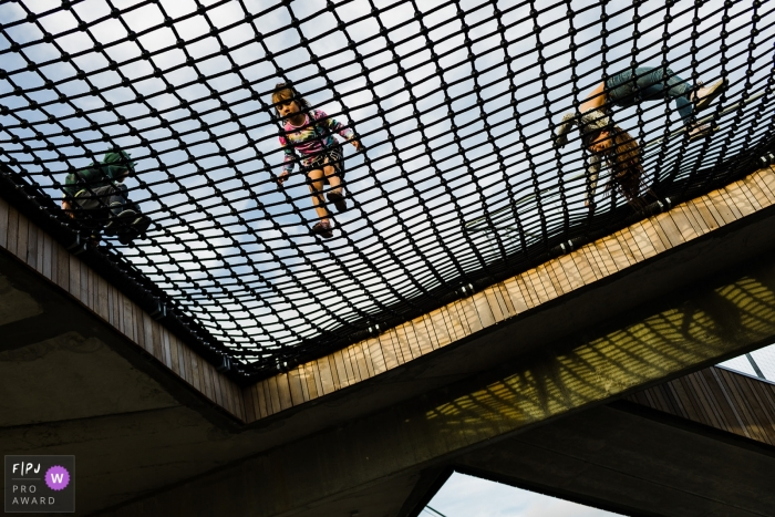Three children play on a net above in this photo recorded by a Copenhagen award-winning, documentary-style family photographer.