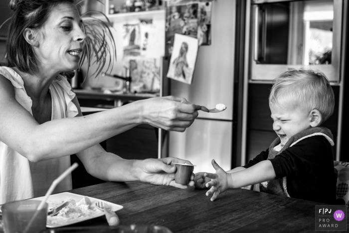 This black and white photo of a toddler refusing to eat his yogurt was captured by a North Rhine-Westphalia documentary family photographer