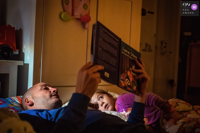 North Rhine-Westphalia documentary family photographer captured this photo of a father and daughter sharing a favorite story in bed